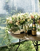 Champagne bottles, glasses and flower on table in garden