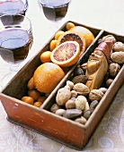 Punch glasses beside box with oranges, nuts & nutcracker