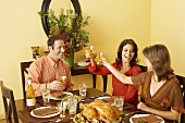 Women Toasting with White Wine Over Thanksgiving Meal