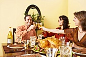 Man and Women Sitting at Thanksgiving Table Toasting with White Wine