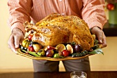 Hands Holding Whole Roasted Thanksgiving Turkey on Platter