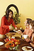 Woman Serving Pie to a Man Sitting a Thanksgiving Table, Woman with Coffee and Pie