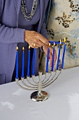 Womans Hand Lighting Manora with Blue Candles