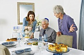 Man Sitting at Table Looking at Hanukkah Dinner Women Placed on Table