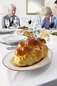 Challah Bread on Hanukkah Table, People Sitting at Table