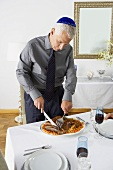 Man Wearing Yamaka Slicing Brisket For Hanukkah Dinner