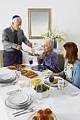 Man Serving Brisket to Woman at Hanukkah Table