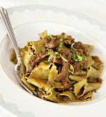 Spinach Pappardelle Topped with Duck Ragu in a Bowl with Fork