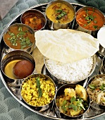 Tray of Assorted Indian Side Dishes with a Bowl of Rice in the Middle