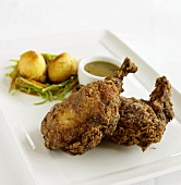 Two Pieces of Crunchy Fried Chicken on a Plate with Dipping Sauce, Potatoes and Vegetables