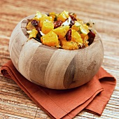 Fruit salad with dried cranberries in wooden bowl