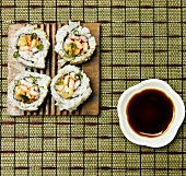 Sushi Rolls on a Plate with Bowl of Soy Sauce For Dipping
