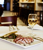 Seared Tuna with Green Beans and a Glass of White Wine on a Restaurant Table