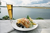 Lobster Roll with Chips, Pickles and a Beer on an Outdoor Table by the Ocean