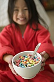 Young Girl Holding Out a Bowl of Fruit Flavored O Cereal