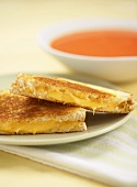 Grilled Cheese Sandwich Cut in Half on a Plate with a Bowl of Soup