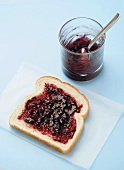 Grape Jelly Spread on a Slice of White Bread, Jelly in a Glass Cup with a Spoon