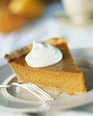 Slice of Pumpkin Pie with a Dollop of Whipped Cream on a Plate; Fork