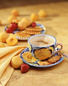 Mug of Cappaccino on a Saucer with Leaf Shaped Cookies; Strawberry and Apricot