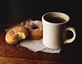 Cup of Coffe with Two Donuts; Bite Taken From One Donut