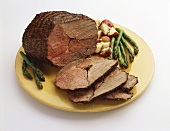 Partially Sliced Roast Beef with Asparagus and Red Potatoes