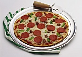A Pepperoni, Sausage, Pepper and Onion Pizza on a Pizza Pan with Cutter