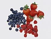 Three Piles of Berries; Blueberries, Strawberries and Raspberries