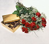 Box of Assorted Chocolates with a Dozen Red Roses on White Background