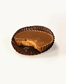 A Peanut Butter Cup with a Bite Taken Out on a White Background