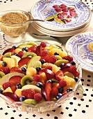 Large Bowl of Fruit Salad with a Small Bowl of Poppy Seed Dressing; Plates