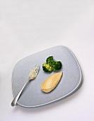 Stück Hähnchenbrust, Baked Potato auf Gabel und Brokkoli