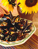 Steamed Mussels Next to a Vase of Sunflowers