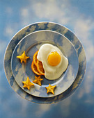 A Fried Egg with Orange Slices and Star Fruit on a Sky Plate and Background