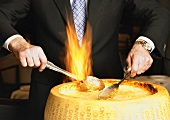 Hands Stirring a Flaming Wheel of Parmesan Cheese