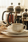 Cup of Coffee with Three French Press Coffee Pots