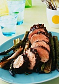 Platter of Sliced Balsamic Roast Pork Loin with Asparagus and Leeks