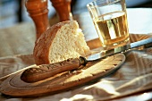 Wedge of Bread on a Cutting Board with Knife and Glass of White Wine