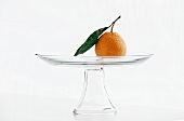 A Single Satsuma Tangerine with Leaf on a Pedestal Dish