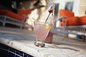Glass of Pink Lemonade on Edge of Pool