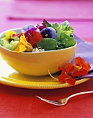 A Salad with Edible Flowers in a Yellow Bowl