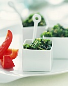 Kale and Nori Salad in Small Square Bowls with Red Pepper Strips