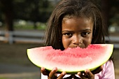 Young Girl Eating a Large Wedge of Watermelon
