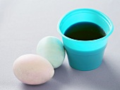 Two Colored Eggs Next to an Easter Egg Coloring Cup