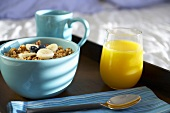 Bowl of Granola Cereal with Juice and Coffee on a Tray in Bed