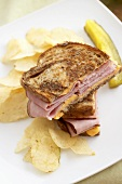 Grilled Ham and Cheese Sandwich Halved with Chips and a Pickle