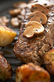 Close Up of Sirloin Steak Topped with Mushrooms on Broiler Pan