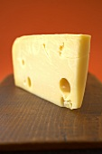 A Wedge of Swiss Cheese on a Wooden Board