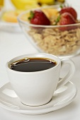 Cup of Black Coffee with Bowl of Cereal on Breakfast Table