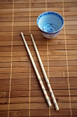 Chopsticks and a Small Empty Cup on a Bamboo Mat