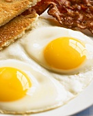 Two Sunny Side Up Fried Eggs with Toast and Bacon, Close Up